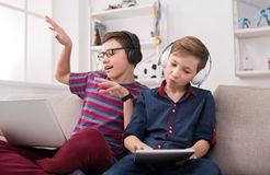 Adolescentes com dispositivos que apreciam a música nos fones de ouvido em casa imagens de stock