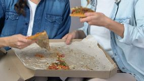 Adolescentes com fome que comem a pizza que senta-se no sofá, comida lixo, serviço da entrega a domicílio video estoque