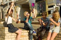 Adolescentes com negativos de observação da foto do filme do interesse e da surpresa, fundo da rua da cidade imagem de stock