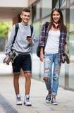 Adolescentes con caminar de los monopatines Fotografía de archivo