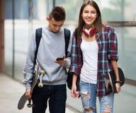Adolescentes con caminar de los monopatines Imagen de archivo