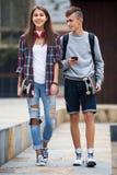 Adolescentes con caminar de los monopatines Foto de archivo libre de regalías
