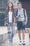 Adolescentes con caminar de los monopatines Fotos de archivo libres de regalías