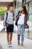 Adolescentes con caminar de los monopatines Imagenes de archivo