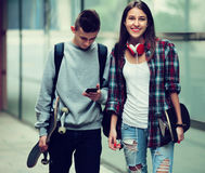 Adolescentes con caminar de los monopatines Fotos de archivo