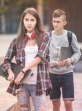 Adolescentes con caminar de los monopatines Fotografía de archivo libre de regalías