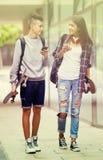 Adolescentes con caminar de los monopatines Imágenes de archivo libres de regalías