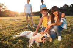 Adolescentes con el perro en parque Imagen de archivo