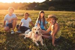 Adolescentes con el perro en parque Fotografía de archivo libre de regalías