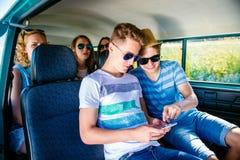 Adolescentes con el smartphone dentro de un campervan viejo, roadtrip Fotografía de archivo