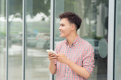 Adolescentes con el teléfono móvil fuera del edificio en ciudad Imagenes de archivo