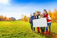 Adolescentes con la bandera en blanco Foto de archivo