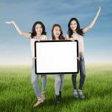 Adolescentes con la cartelera en prado Fotos de archivo
