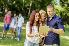 Adolescentes con la tableta en el parque Imagen de archivo libre de regalías