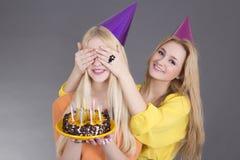 Adolescentes con la torta de cumpleaños Imagen de archivo libre de regalías