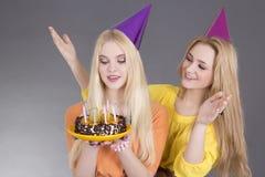 Adolescentes con la torta de cumpleaños sobre gris Foto de archivo libre de regalías
