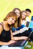 Adolescentes con las computadoras portátiles Imágenes de archivo libres de regalías
