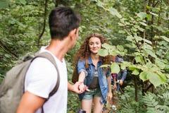 Adolescentes con las mochilas que caminan en vacaciones de verano del bosque Fotos de archivo