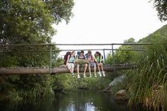 Adolescentes con las mochilas que leen el mapa en el puente Fotografía de archivo
