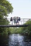 Adolescentes con las mochilas que leen el mapa en el puente Fotografía de archivo libre de regalías