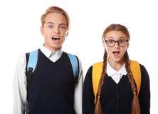 Adolescentes con las mochilas que se colocan en el fondo blanco Fotografía de archivo