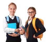 Adolescentes con las mochilas que sostienen los libros en el fondo blanco Fotografía de archivo libre de regalías