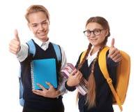 Adolescentes con las mochilas que sostienen los libros en el fondo blanco Fotos de archivo libres de regalías