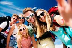 Adolescentes con las mochilas que toman el selfie, festival del verano Fotografía de archivo