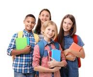 Adolescentes con las mochilas y los cuadernos en el fondo blanco Foto de archivo libre de regalías