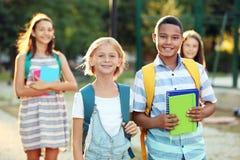 Adolescentes con las mochilas y los cuadernos que caminan en parque fotografía de archivo