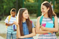 Adolescentes con las mochilas y los cuadernos que caminan en parque Imagenes de archivo