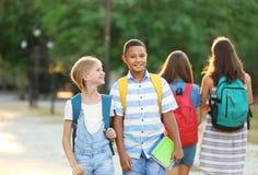Adolescentes con las mochilas y los cuadernos que caminan en parque Fotos de archivo