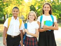 Adolescentes con las mochilas y los cuadernos que caminan en parque Fotografía de archivo libre de regalías