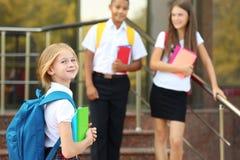 Adolescentes con las mochilas y los cuadernos que se colocan en las escaleras de la escuela Fotografía de archivo
