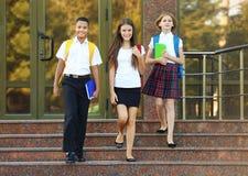 Adolescentes con las mochilas y los cuadernos que se colocan en las escaleras de la escuela Fotos de archivo