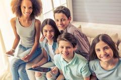 Adolescentes con los artilugios en casa Imagen de archivo libre de regalías