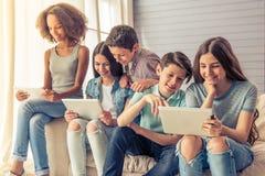 Adolescentes con los artilugios en casa Fotos de archivo libres de regalías
