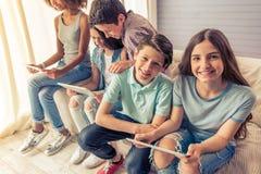 Adolescentes con los artilugios en casa Fotos de archivo