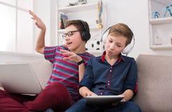 Adolescentes con los artilugios que disfrutan de música en auriculares en casa Imagenes de archivo