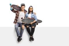 Adolescentes con los longboards que se sientan en un panel Fotos de archivo