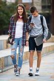 Adolescentes con los monopatines al aire libre Imagen de archivo libre de regalías