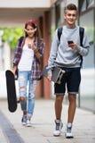Adolescentes con los monopatines al aire libre Imagen de archivo