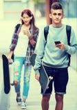 Adolescentes con los monopatines al aire libre Fotos de archivo