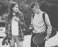 Adolescentes con los monopatines al aire libre Foto de archivo