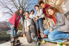 Adolescentes con los monopatines o los rollerblades Imagen de archivo libre de regalías