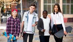 Adolescentes con los monopatines que presentan en plaza Imagenes de archivo