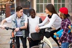 Adolescentes con los monopatines que presentan en plaza Fotografía de archivo libre de regalías