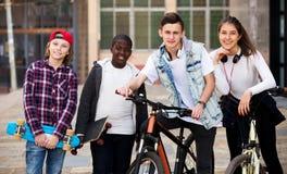 Adolescentes con los monopatines que presentan en plaza Fotografía de archivo