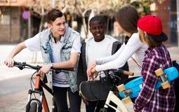 Adolescentes con los monopatines que presentan en plaza Foto de archivo libre de regalías