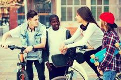 Adolescentes con los monopatines que presentan en plaza Imagen de archivo